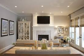 recessed lighting over fireplace comfy living room with wall mounted tv above a fireplace and using
