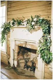 fireplace mantle with white rose and eucalyptus garland by stems