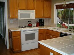 brown wooden kitchen cabinet with white granite gas stove with