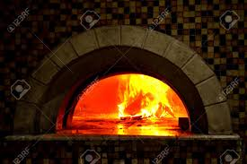 image detail of a wood fired pizza oven with fire blazing stock