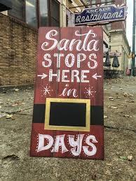 santa stops here in days rustic wood sign at walking