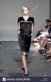 model with short blonde hair blue eye shadow black satin dress