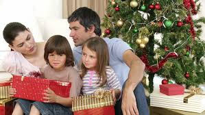 family opening gifts while sitting on the floor in the