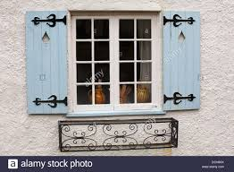 pots in window with light blue shutters and wrought iron window