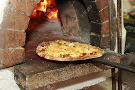 gourmet pizza coming out fired pizza oven in restaurant