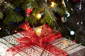 christmas gifts under the christmas tree with a red ribbon stock