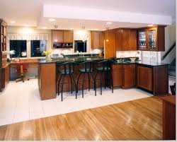 classy kitchen with white breakfast bar table and cafe stools in welcoming kitchen with maple cabinetry also ceramic floor