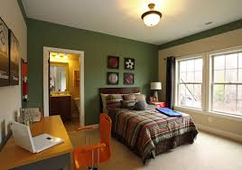 dark green bedroom wall with orange chair and brown wooden desk