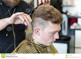 young man on a haircut in the barber shop stock photo image