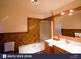 glass screen on bath in modern bathroom with terracotta wall tiles