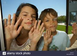 the glass door boy and sticking their nose on the glass door stock photo