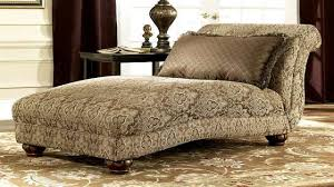 ornate brown fabric double chaise chair with round wooden legs of