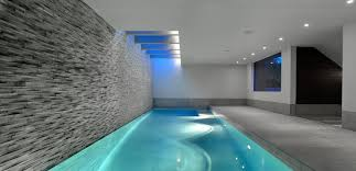great looking indoor swimming pool design with grey brick wall and