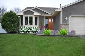 modern grey wall house with white door and garden in front of