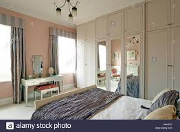bedroom with bed furniture cupboards and mirror in london house