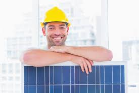 le bureau solaire travailleur manuel de sourire avec le panneau solaire dans le bureau