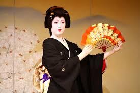 Japan Geisha Dreams   InsideJapan Blog Geisha in flamboyant kimono protecting her makeup with a fan  Kyoto  Japan