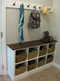 white wall shelf with hooks and baskets