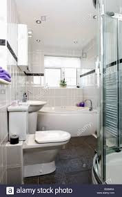 modern grey tiled bathroom with white toilet and bath and slate