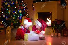family eve fireplace kids opening presents children tree stock