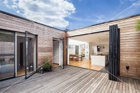 falttür küche holzterrasse eines zeitgenössischen wohnhauses mit holzverschalung