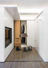 390 square feet small apartment utilizes a sliding wall to hide its functions