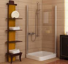 bathroom towel storage and corner shower stall with tile walls