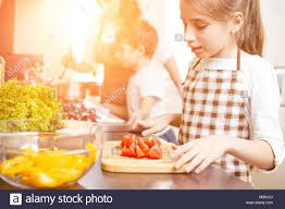 young teenage cooking together with her family in the kitchen
