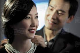 man pearl necklace images Young man putting a pearl necklace on a woman stock photo dissolve jpg
