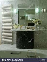 wall lights on either side of mirror above marble topped vanity