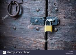 modern yellow padlock on the metal bracket on the old wooden door
