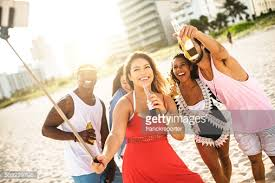 Take A Selfie Friends Laughing While Taking A Selfie At The Beach Stock Photo