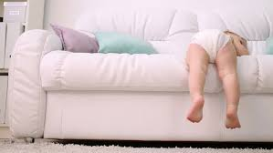 back of kid in diaper climbing down from white sofa at home stock