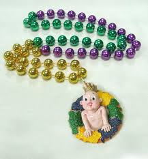 mardi gras specialty mardi gras king cake and baby on a purple green gold specialty bead