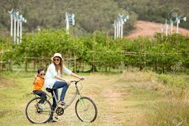 cycling wind woman and boy riding bicycle in farm with wind turbines in