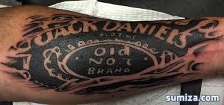 typical blackwork style arm tattoo of jack daniels bottle