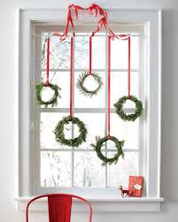 tiny wreaths hung with red ribbon in a window decoist
