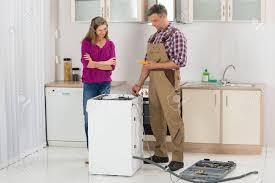 lave linge dans la cuisine femme regardant homme technicien contrôle lave linge dans la cuisine