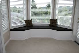 white serene bay window seats with black cushions and pillows also