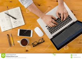 tech hipster working at wooden desk on laptop stock photo image