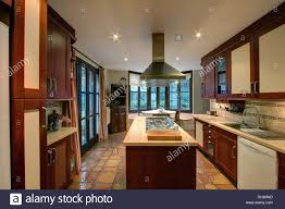 modern spanish kitchen large chrome extractor above hob in island unit in modern spanish