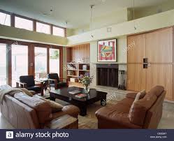 brown leather sofas in modern double height living room with large