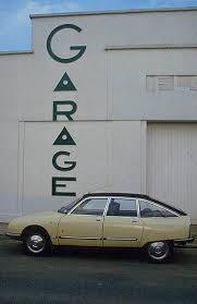 motor citroën gs pallas poses before an art déco garage facade