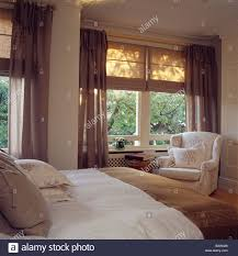 cream linen blinds and brown voile curtains on windows in cream