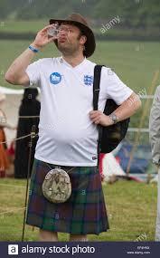a man in a scottish kilt wearing an england football shirt and