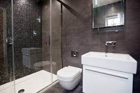 black ensuite with large floor and ceiling tiles and black mosaics