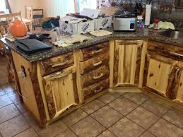 hand made rustic aspen log kitchen cabinets and built in wall