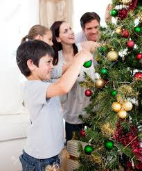 happy family decorating a christmas tree with boubles stock photo