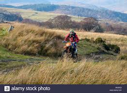 motocross bikes for sale in wales a man riding a dirt bike on a multi use track through countryside