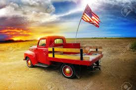 American Flag Sunset Red Vintage Pick Up Truck With American Flag In Wide Open Country